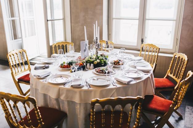 Feestelijke eettafel ingericht voor veel mensen, smakelijke gerechten, kandelaar in het midden, wit tafelkleed, ruim gezellig luxe restaurant