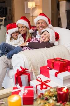 Feestelijke familie die in santahoed op laag koestert