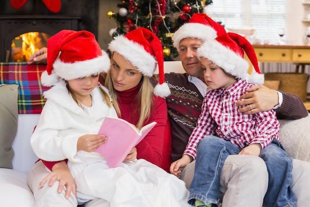 Feestelijke familie die santahoed draagt terwijl het lezen op de laag