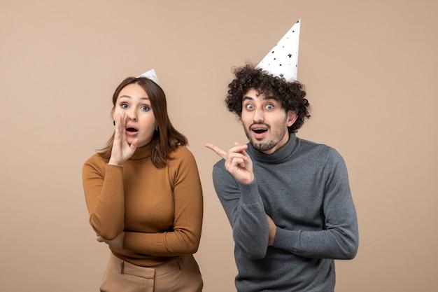 Feestelijke feestdagen en feest concept - blij emotioneel opgewonden verrast mooi jong koppel spreken over iets op grijs