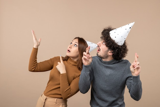 Feestelijke feestdagen en feest concept - gelukkig emotioneel opgewonden jong koppel verrast op grijs
