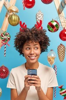 Feestelijke geest in de lucht. vrolijk kerstfeest concept. blij dat donkere vrouw smartphone gebruikt om felicitaties te sturen voor familieleden poses in ingerichte kamer kijkt gelukkig opzij glimlachen. nieuwjaar is binnenkort