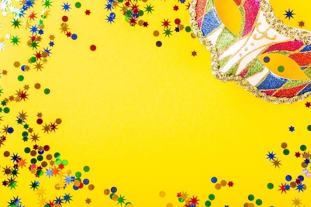 Feestelijke gele ondergrond met kleurrijk carnaval masker. wenskaartconcept voor verjaardag, carnaval, feest. kopieer ruimte, bovenaanzicht, plat leggen