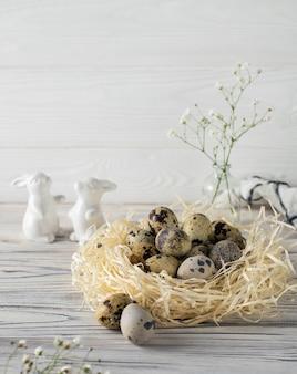 Feestelijke gelukkige pasen-decoratie met kwartelseieren en ceramische konijntjes