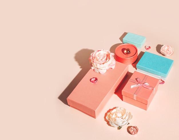 Feestelijke geometrische opstelling van geschenkdozen en bloemen in pastelkleuren met zonnige schaduwen