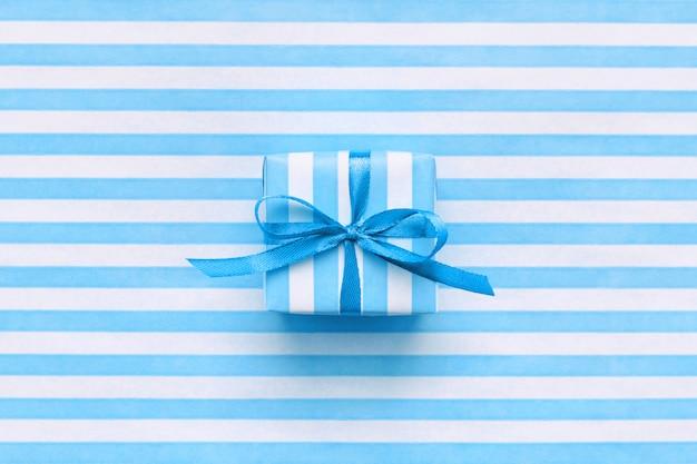 Feestelijke geschenkdoos op blauw en wit gestreept inpakpapier