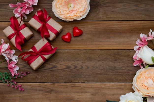 Feestelijke geschenkdozen en boeket bloemen op houten achtergrond met kopie ruimte. valentijnsdag, liefde.
