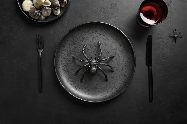 Feestelijke halloween-tafelsetting met spin en zwart decor
