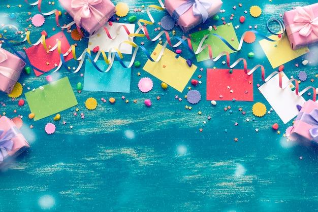 Feestelijke heldere blauwe decoratie als achtergrond voor de vakantie gekleurde doos van confettien kronkelige document giften