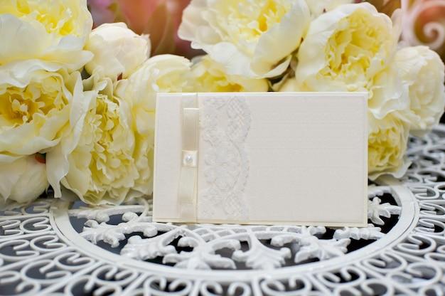 Feestelijke huwelijksuitnodiging in een zachte stijl op een achtergrond van bloemen.