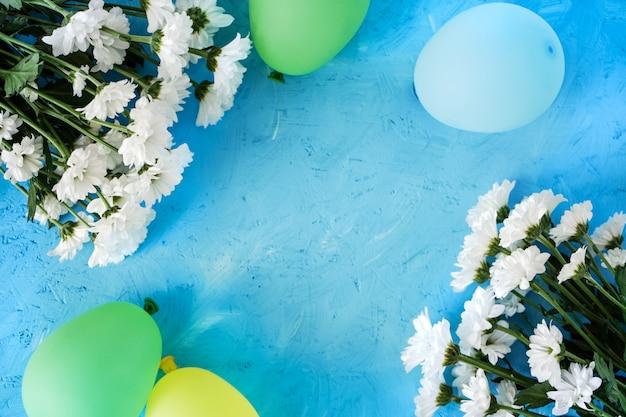 Feestelijke indeling, verjaardag. witte camomiles en geel-blauwe ballen op een blauwe houten tafel.