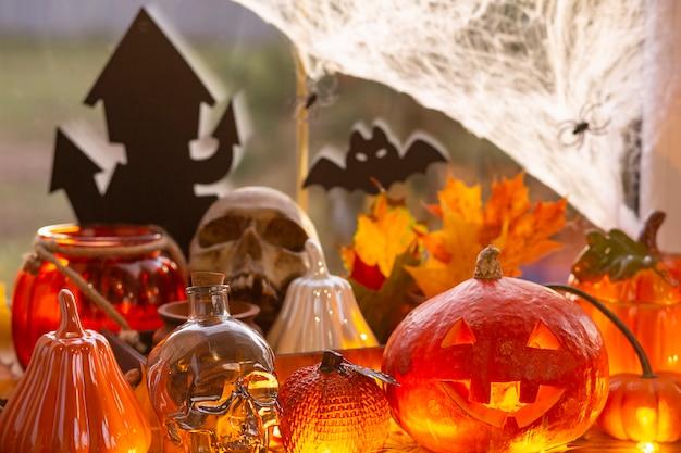 Feestelijke inrichting van het huis op de vensterbank voor halloween - pompoenen, jack o lantaarns, schedels, vleermuizen, spinnenwebben, spinnen, kaarsen en een slinger - een gezellige en vreselijke sfeer