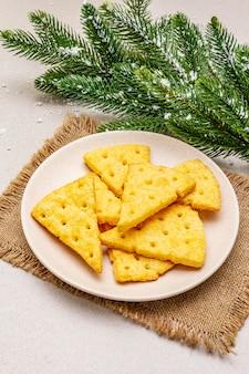 Feestelijke kaascrackers, nieuwjaar snackconcept. koekjes, sparrentak, kunstmatige sneeuw, juteservet.