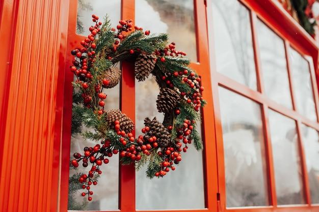 Feestelijke kerst adventskrans hangt buiten bij raam