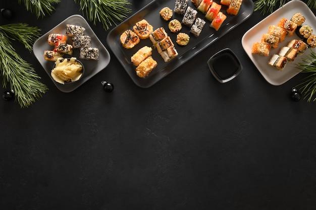 Feestelijke kerst aziatisch eten met sushi set, vakantie decoratie op zwarte achtergrond. nieuwjaarsfeest.