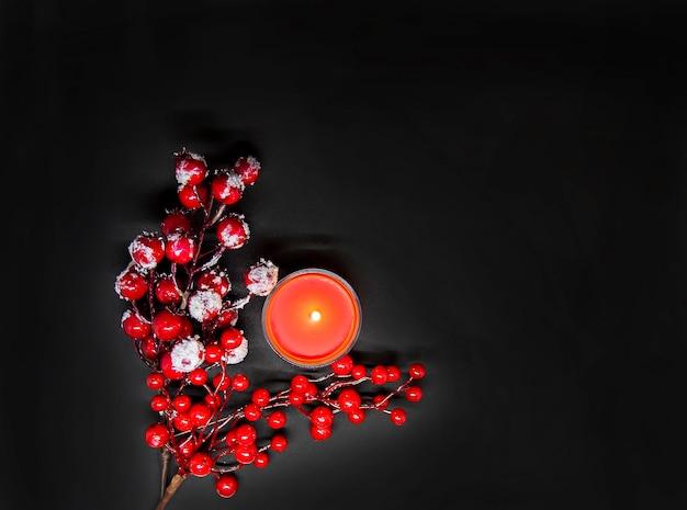 Feestelijke kerst- of nieuwjaarssamenstelling met rode hulstbessen in sneeuw en brandende waskaars.
