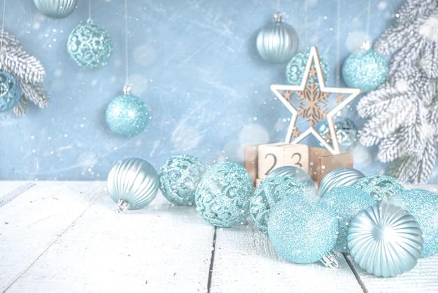 Feestelijke kerst- of winterdecoratie met blauwe zilveren kerstboomballen op lichtblauw