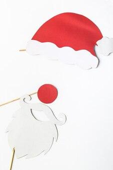 Feestelijke kerstdecoratie witte baard bril en rode kerstmuts op stokken