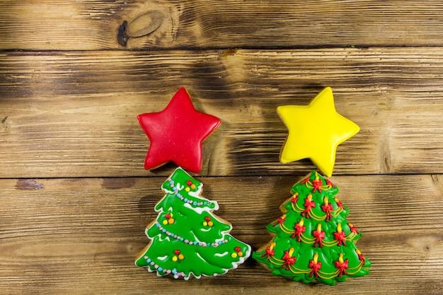 Feestelijke kerstkoekjes in de vorm van een kerstboom en sterren. lekkere peperkoeken op houten tafel. bovenaanzicht