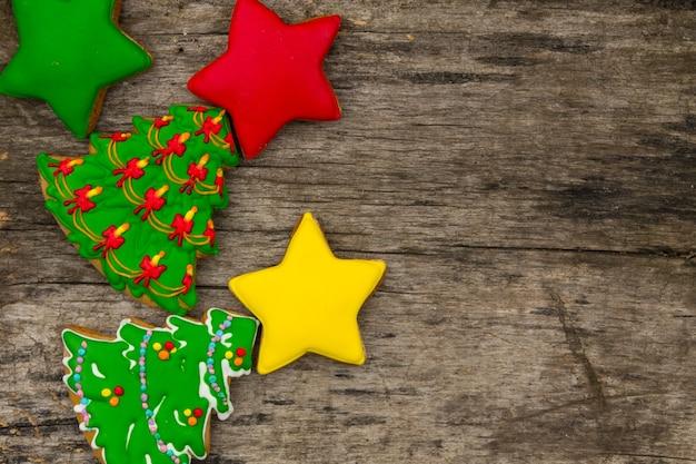 Feestelijke kerstkoekjes in de vorm van een kerstboom en sterren. lekkere peperkoeken op rustieke houten tafel. bovenaanzicht