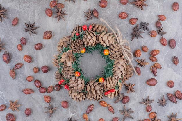 Feestelijke kerstkrans met dennenappels en steranijs op marmeren achtergrond.