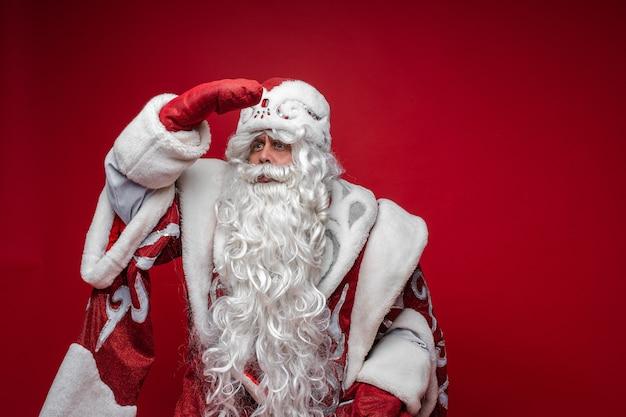 Feestelijke kerstman kijkt in de verte met de hand op het voorhoofd