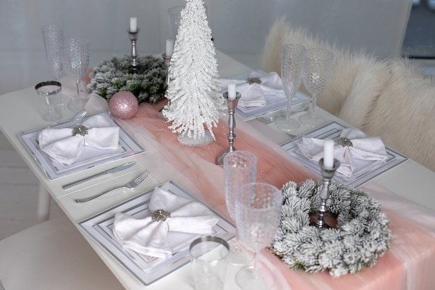 Feestelijke kersttafel met tafelkleed tussen winterversieringen en witte kaarsen