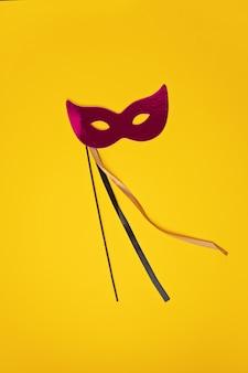 Feestelijke, kleurrijke mardi gras of carnaval masker en accessoires over gele muur. plat leggen, bovenaanzicht, kopie ruimte