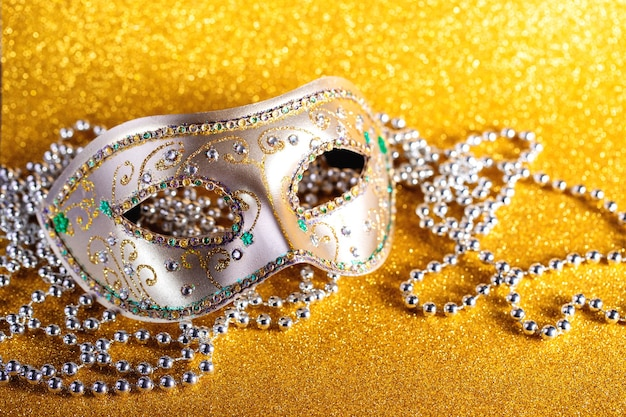 Feestelijke kleurrijke mardi gras of carnivalemasker en kralen op gouden achtergrond venetiaanse maskers uitnodiging voor feestje wenskaart venetiaanse carnaval viering concept