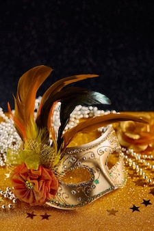 Feestelijke kleurrijke mardi gras of carnivalemasker met veren en kralen op gouden achtergrond venetiaanse maskers uitnodiging voor feestje wenskaart venetiaanse carnaval viering concept