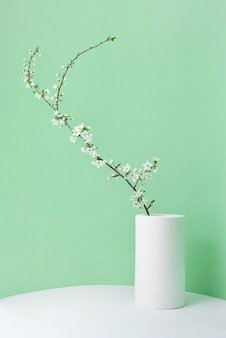 Feestelijke lentekaart met verse natuurlijke bloeiende kersenbloemen tak in een keramische vaas