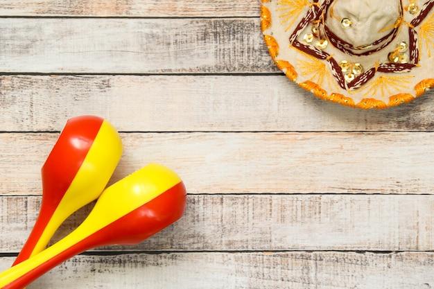Feestelijke mexicaanse hoofdtooi op een houten bord en rode en gele plastic maracas.