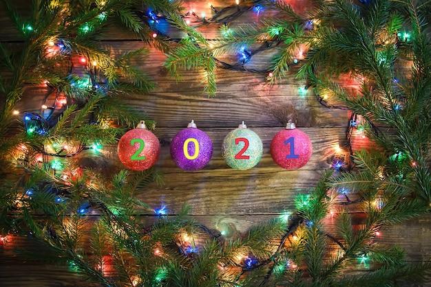 Feestelijke mooie nieuwe jaar achtergrond met kleurrijke kerstballen en lampjes op een houten achtergrond