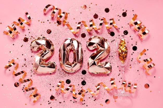 Feestelijke nieuwjaar flatlay achtergrond roze goud folie ballonnen en chrtistmas decoraties. bovenste horizontale weergave copyspace.