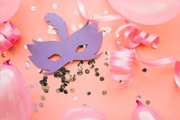 Feestelijke opstelling van confetti met papieren masker