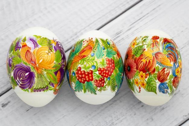 Feestelijke paas geschenkenkaart. kleurrijke eieren op houten witte achtergrond. paasdecoratie.