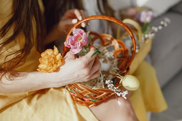 Feestelijke paasmandje in handen van een vrouw in een gele jurk