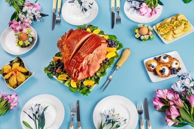 Feestelijke paastafel met ham, salade en pannenkoeken. paasdiner.