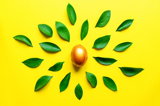 Feestelijke pasen-achtergrond. gouden, stijlvolle pinted ei met ruskus bladeren op gele achtergrond.
