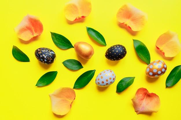 Feestelijke pasen-achtergrond. gouden, zwart en wit stijlvolle pinted eieren met bladeren en rozenblaadjes op gele achtergrond.