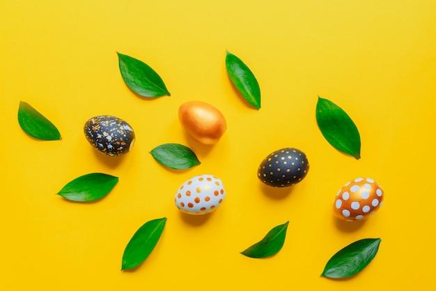 Feestelijke pasen-achtergrond. gouden, zwart en wit stijlvolle pinted eieren met bladeren op gele achtergrond.