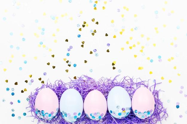Feestelijke pasen-achtergrond met verfraaide eieren, bloemen, suikergoed en linten in pastelkleuren op wit. kopieer ruimte