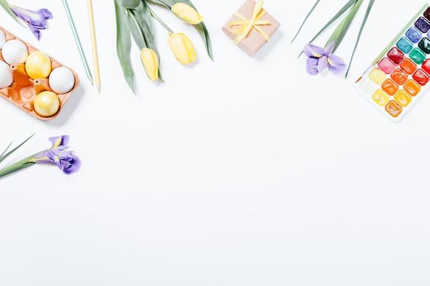 Feestelijke pasen arrangement van bloemen, beschilderde eieren en waterverf
