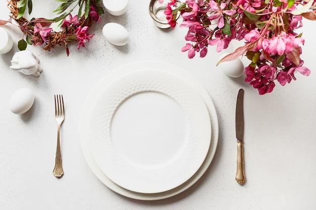 Feestelijke pasen-tabel met bloeiende appelbloemen op witte tafel.