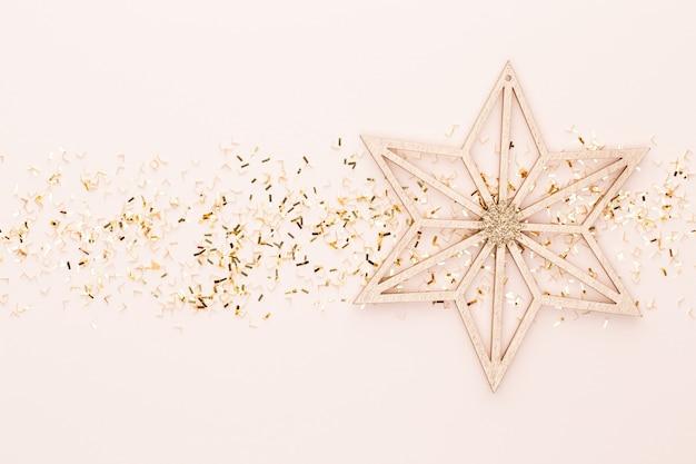 Feestelijke pastel achtergrond. kerststerren en glanzende glitter, confetti op pastel achtergrond