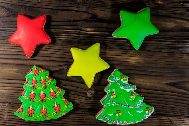 Feestelijke peperkoek kerstkoekjes in de vorm van een kerstboom en sterren op houten tafel. bovenaanzicht
