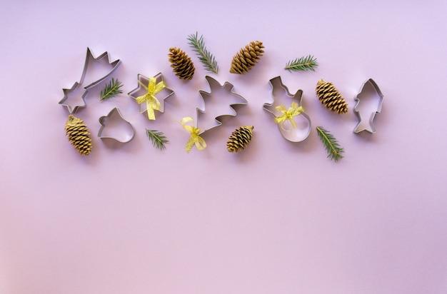 Feestelijke plat leggen van kerstkoekjessnijders met dennentakken en kegels op een lila achtergrond. ruimte voor tekst.