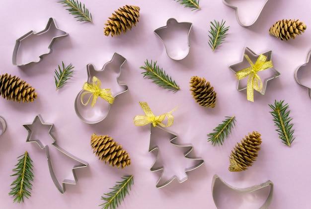 Feestelijke plat leggen van kerstkoekjessnijders met dennentakken en kegels op een lila achtergrond.