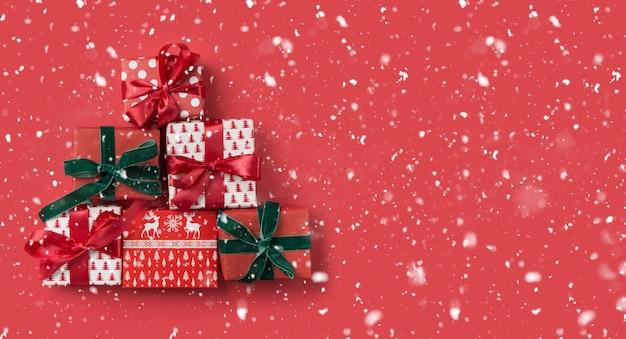 Feestelijke rode geschenken als kerstboom op rode besneeuwde achtergrond voor wenskaart. xmas banner voor tweede kerstdag. uitzicht van bovenaf, plat leggen. sjabloon, mockup.