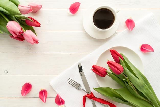 Feestelijke romantische tafelsetting met zilveren bestek en fris roze tulpenboeket.